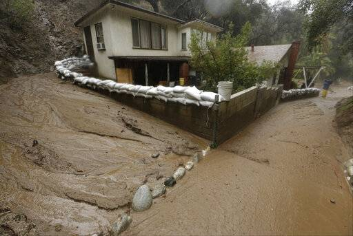 A mud flow skirts a house protected with sandbags in Monrovia, Calif. Federal forecasters say an El Nino, which alters weather worldwide, has formed but is so weak and late that it shouldn't be a big deal.