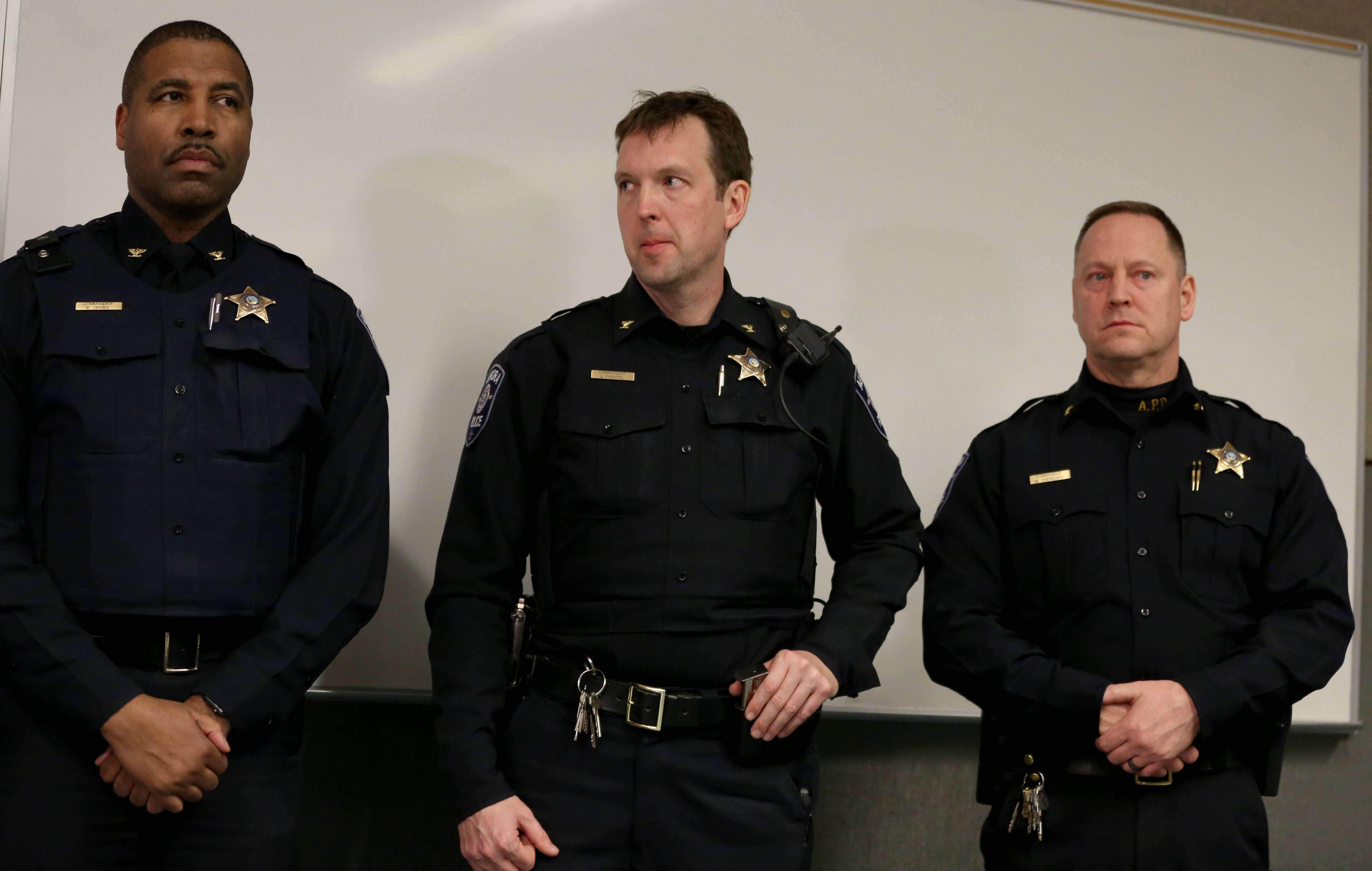 Aurora officers listen during a Friday night news conference as Police Chief Kristen Ziman speaks about officers who were wounded.