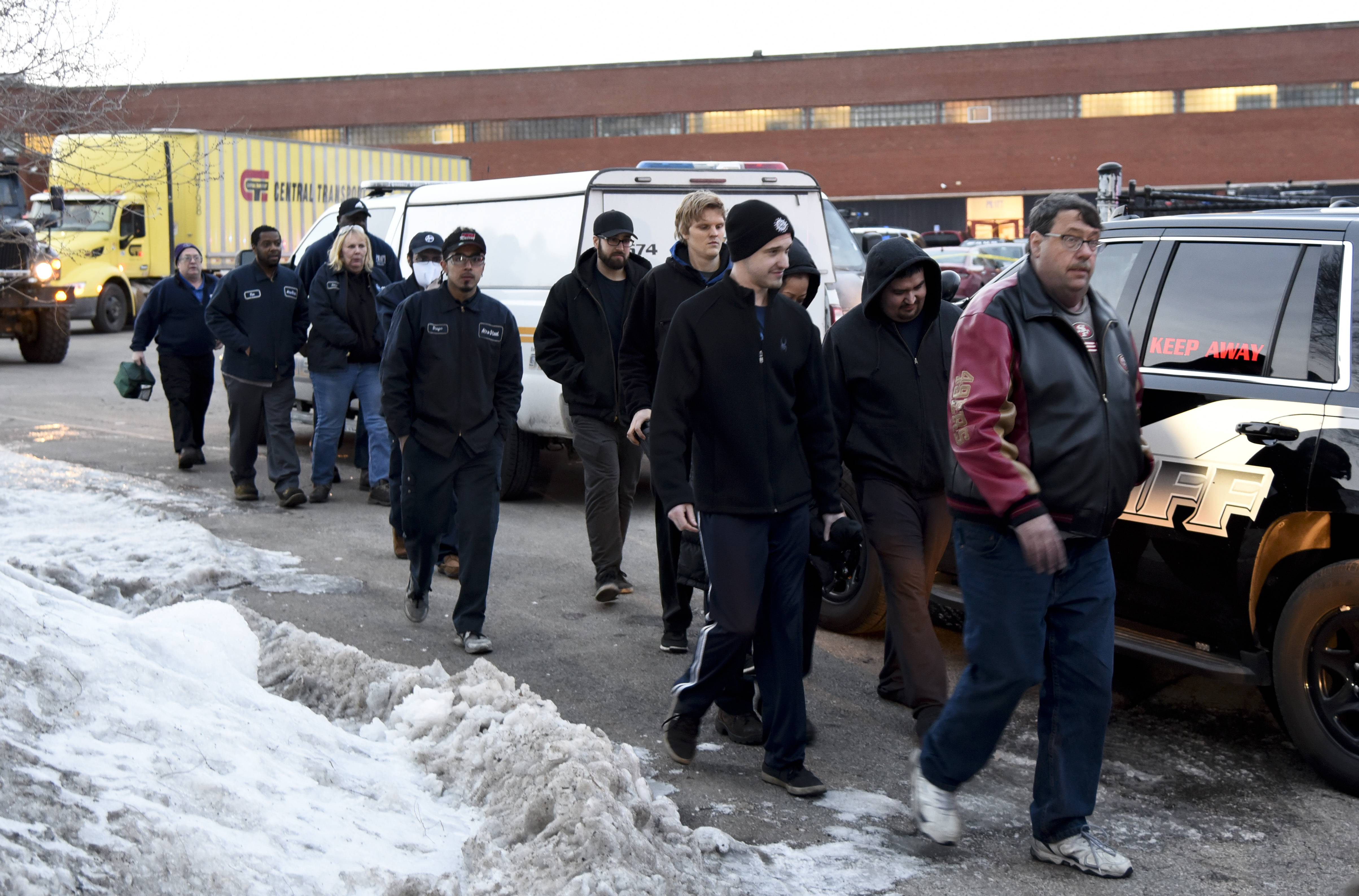 Employees are escorted from the scene of Friday's mass shooting at the Henry Pratt warehouse in Aurora.