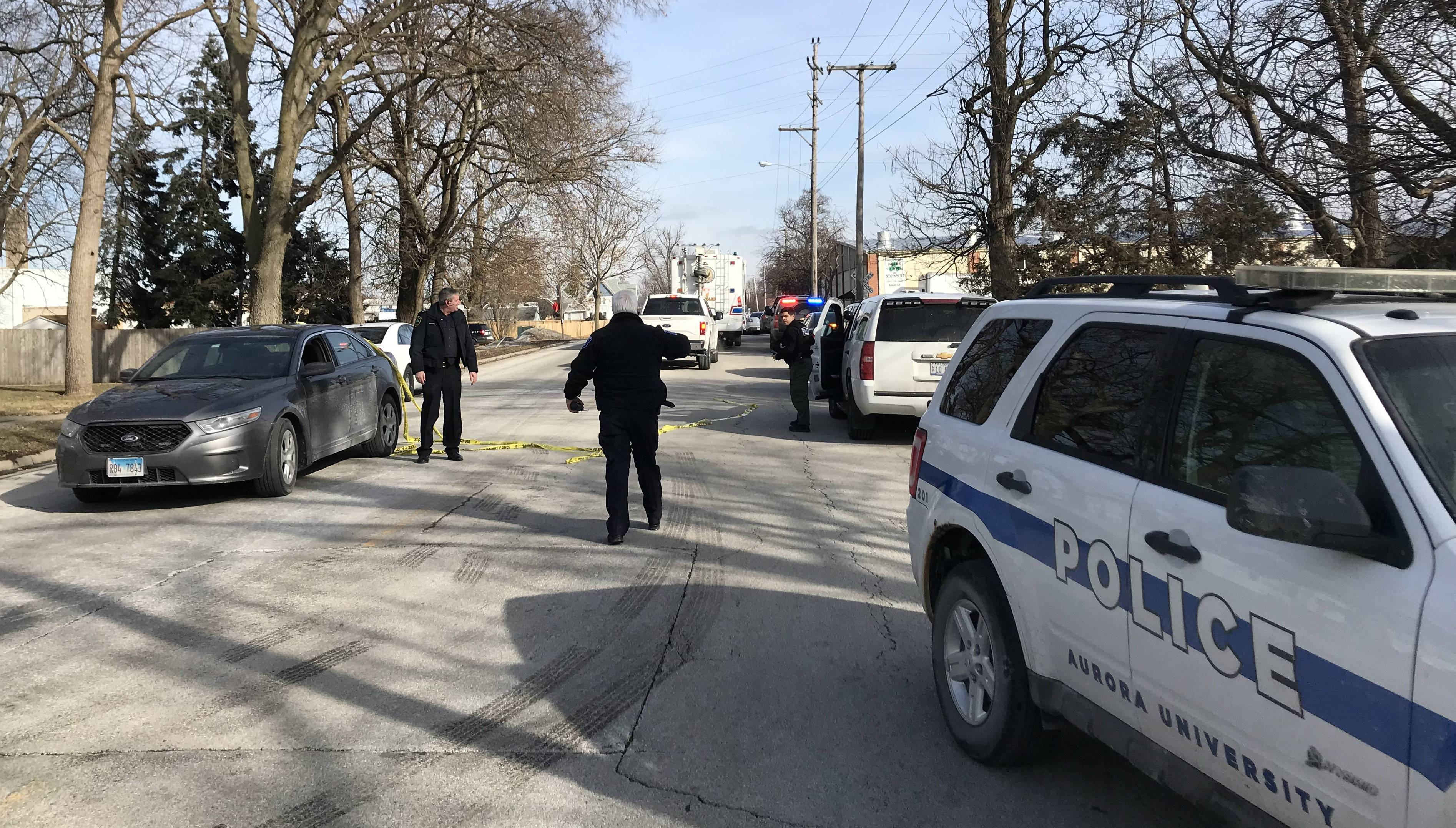 Police officers from throughout the suburbs respond to a mass shooting in Aurora that left six people dead, including the shooter, and wounded five police officers and multiple civilians.