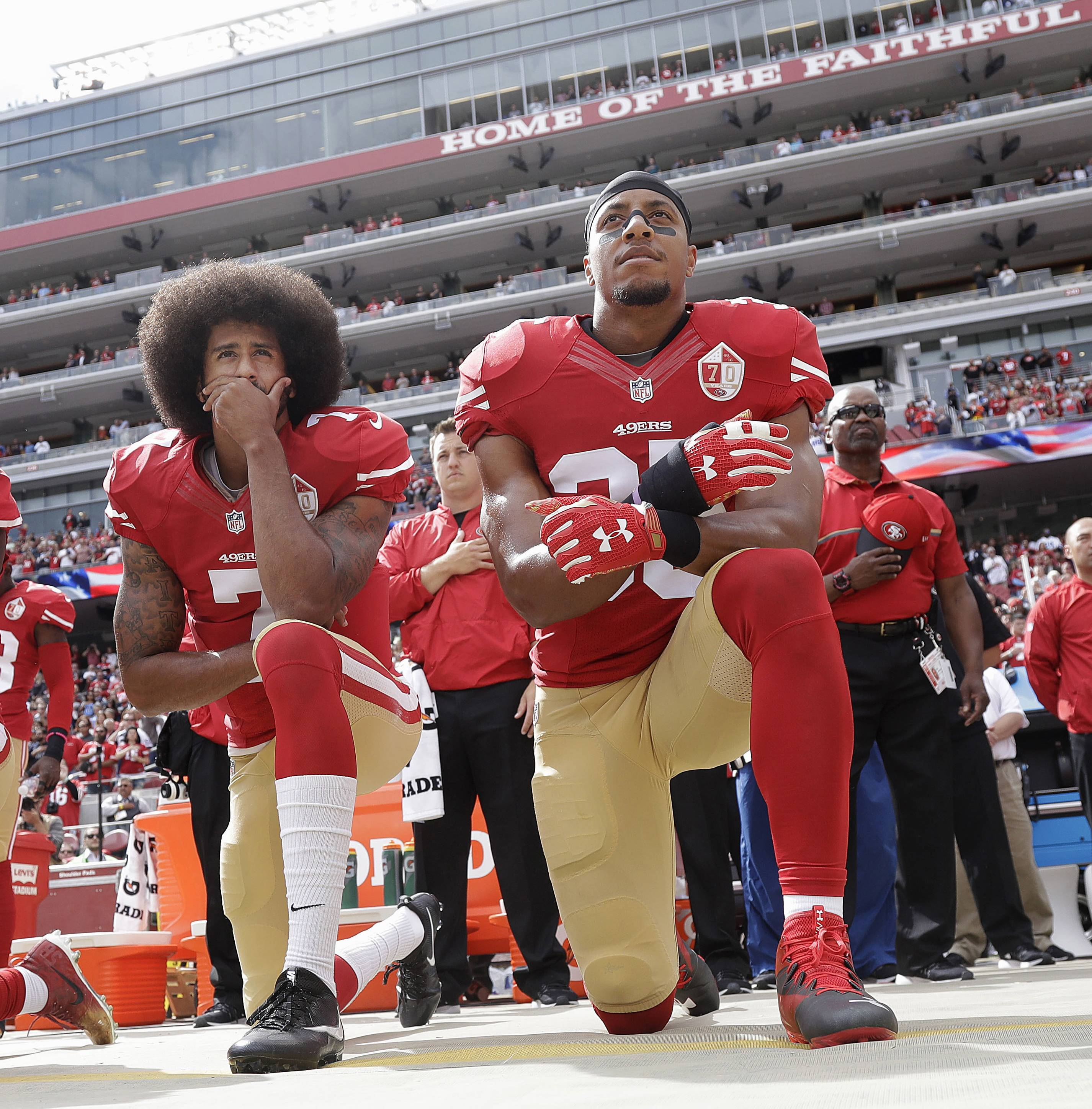 San Francisco 49ers quarterback Colin Kaepernick, left, and safety Eric Reid kneel during the national anthem before a against the Dallas Cowboys. Colin Kaepernick and Eric Reid have reached settlements on their collusion lawsuits against the NFL, the league said Friday.