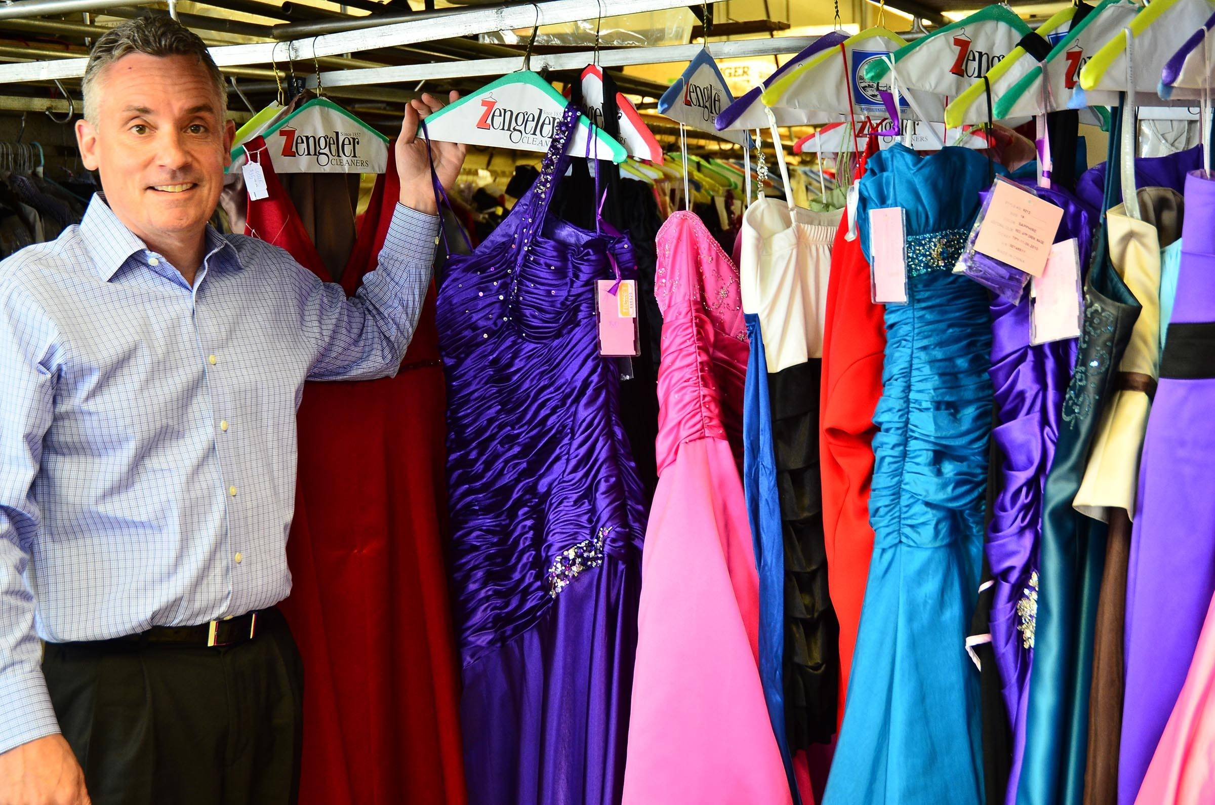 Tom Zengeler, president of Zengeler Cleaners, is pictured with dress previously donated to the Glass Slipper Project.