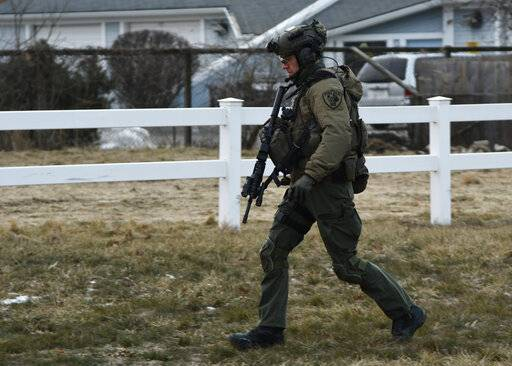 A law enforcement officer works at the scene of a shooting at the Henry Pratt Co. on Friday, Feb. 15, 2019, in Aurora, Ill. Officials say several people were killed and at least five police officers were wounded after a gunman opened fire in an industrial park. (AP Photo/Matt Marton)