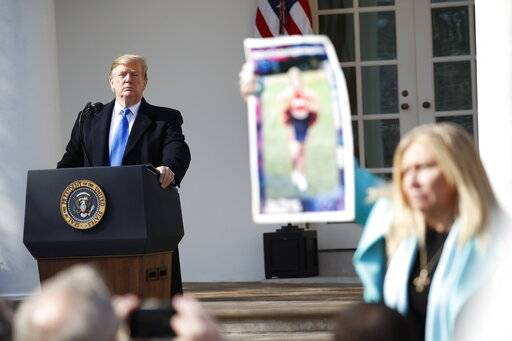 President Donald Trump looks on as an Angel Mom holds up a poster of her daughter, during an event in the Rose Garden at the White House to declare a national emergency in order to build a wall along the southern border, Friday, Feb. 15, 2019 in Washington.