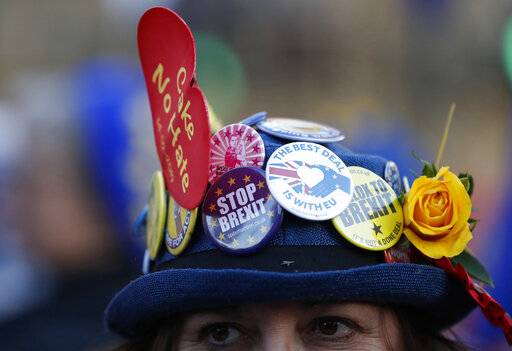 An anti-Brexit demonstrator wears a hat adorned with anti Brexit statements as she protests outside the Palace of Westminster in London, Thursday, Feb. 14, 2019. British lawmakers are holding another series of votes on Brexit legislation Thursday. (AP Photo/Alastair Grant)