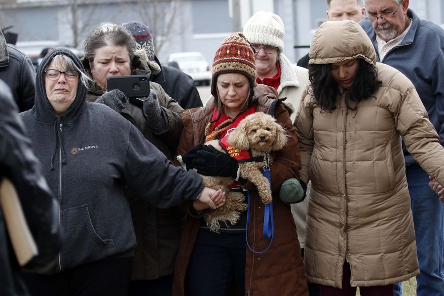 Nancy Herron, of Aurora, left, and Aimee Maas, of Wheaton, holding her dog Paddington, gather with others Saturday for a prayer vigil outside the site of a workplace shooting in Aurora in which five employees were killed, five police officers and another civilian were wounded, and ended with the shooter's own death.