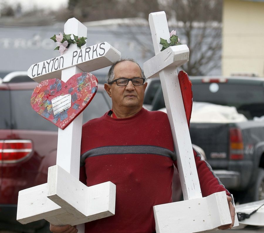 Greg Zanis of Aurora replaces crosses without names with new crosses with victims' names on them outside the site of an Aurora workplace shooting that killed five employees, wounded five police officers and another civilian, and ended with the shooter's own death. The names were announced at a police news conference Saturday morning.