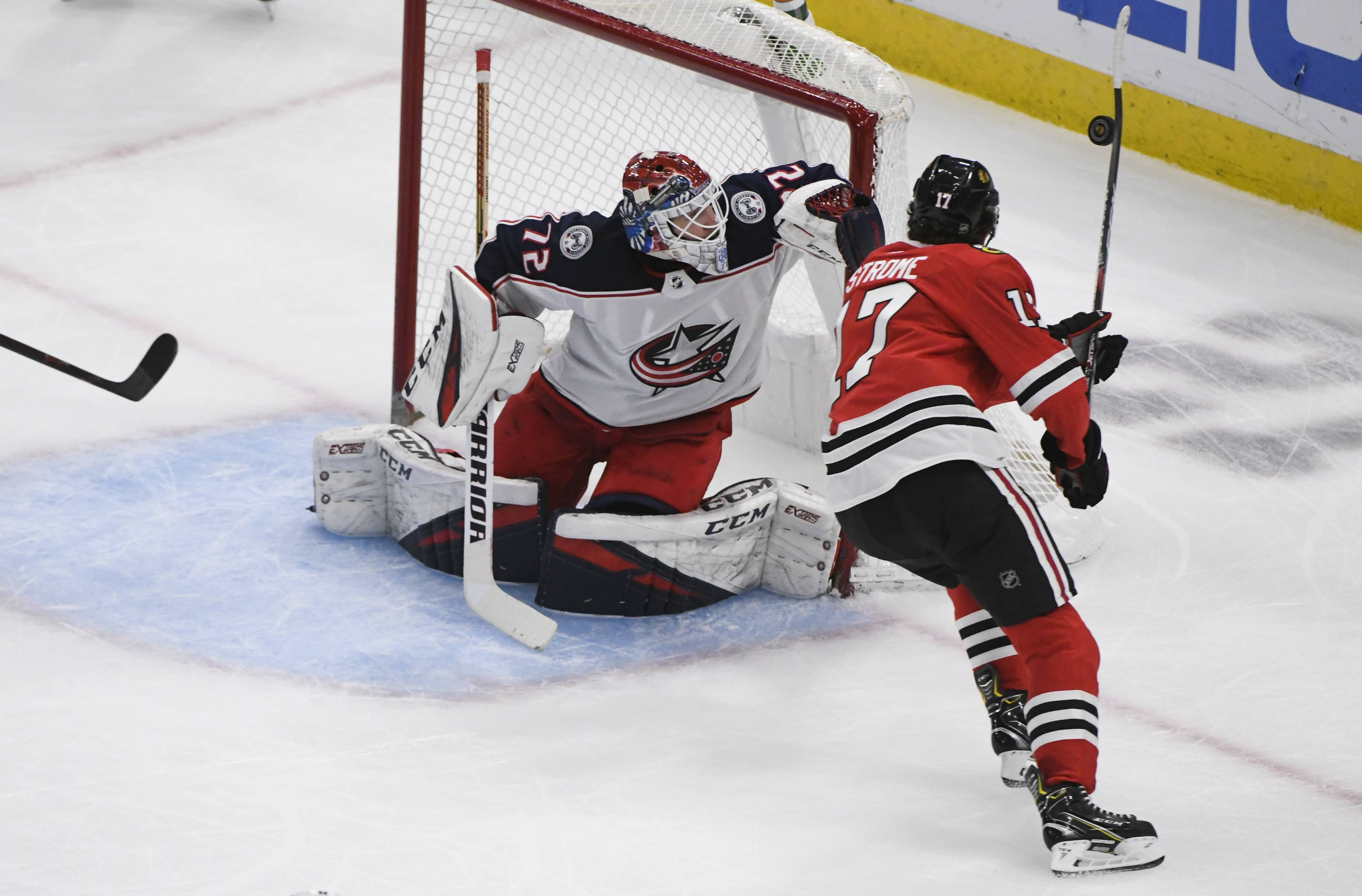 Columbus Blue Jackets goaltender Sergei Bobrovsky (72) defends against Chicago Blackhawks center Dylan Strome (17), who tries to knock down the puck during the second period of an NHL hockey game Saturday, Feb. 16, 2019, in Chicago. (AP Photo/Matt Marton)