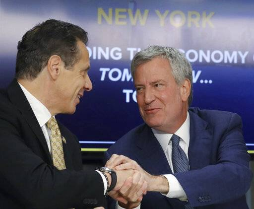 FILE - In this Nov. 13, 2018 file photo, New York Gov. Andrew Cuomo, left, and New York City Mayor Bill de Blasio shake hands during a news conference in New York. Cuomo and de Blasio trumpeted Amazon's decision to build a $2.5 billion campus in the Queens borough of New York as a major coup. Neither one expected the near immediate local backlash that would cause Amazon to cancel their plans on Feb. 14, 2019. (AP Photo/Bebeto Matthews, File)