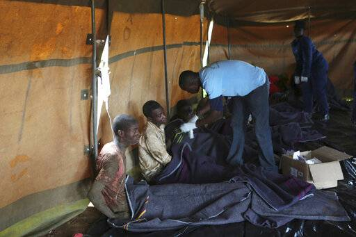 Survivors of artisanal miners sit in a tent after rains flooded mines on the outskirts of Kadoma, west of Harare, Zimbabwe, Saturday, Feb, 16, 2019. About 40 people were trapped underground, said a police spokesman. (AP Photo/Tsvangirayi Mukwazhi)