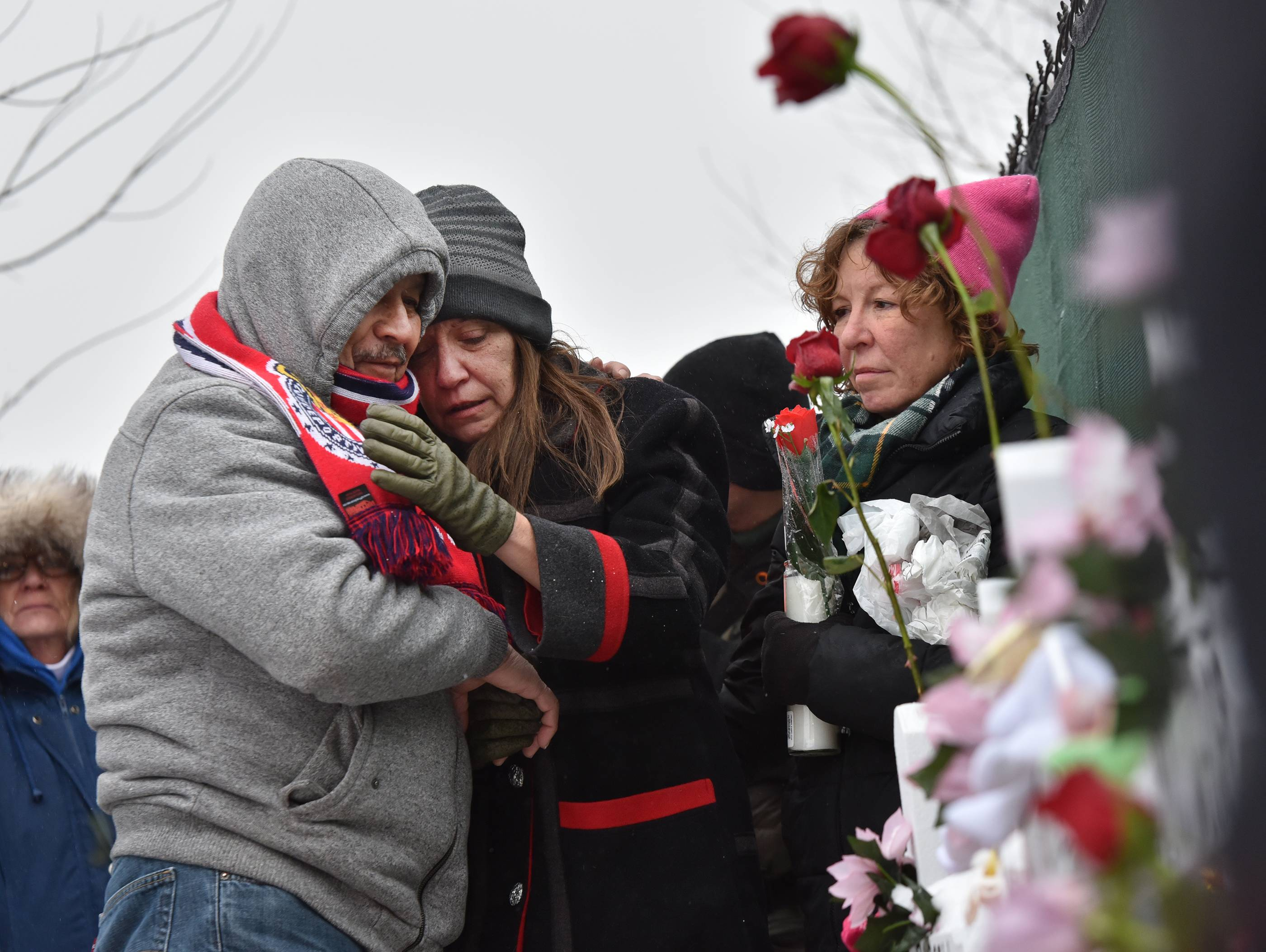 Jeff Knox/jknox@dailyherald.comMourners place a flower at the crosses outside of the Henry Pratt company in Aurora on Sunday, Feb. 17 in memory of the 5 employees killed on Friday.