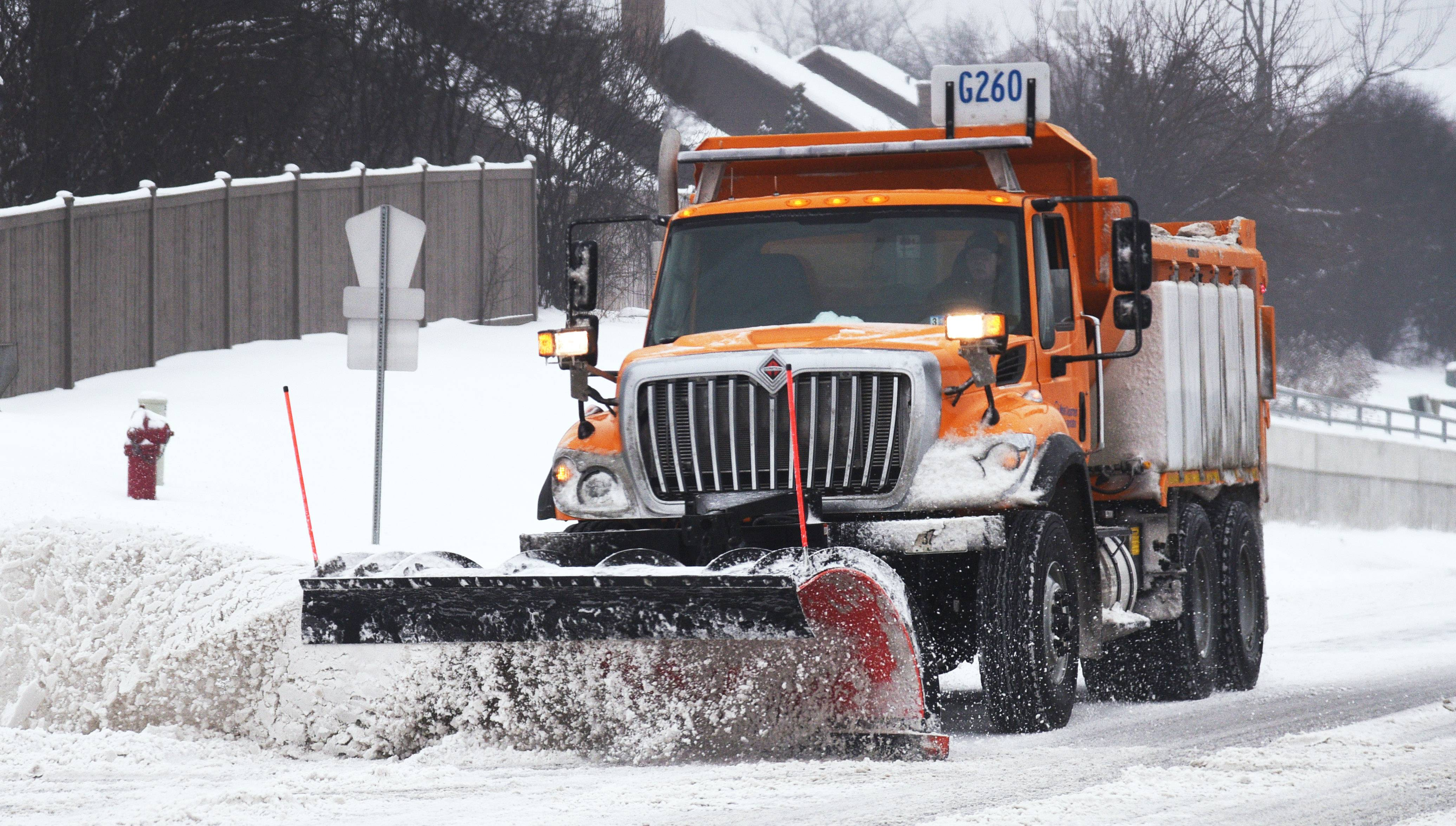 A plow clears snow at Route 12 and Ela Road in Lake Zurich last week in another storm hitting the suburbs.