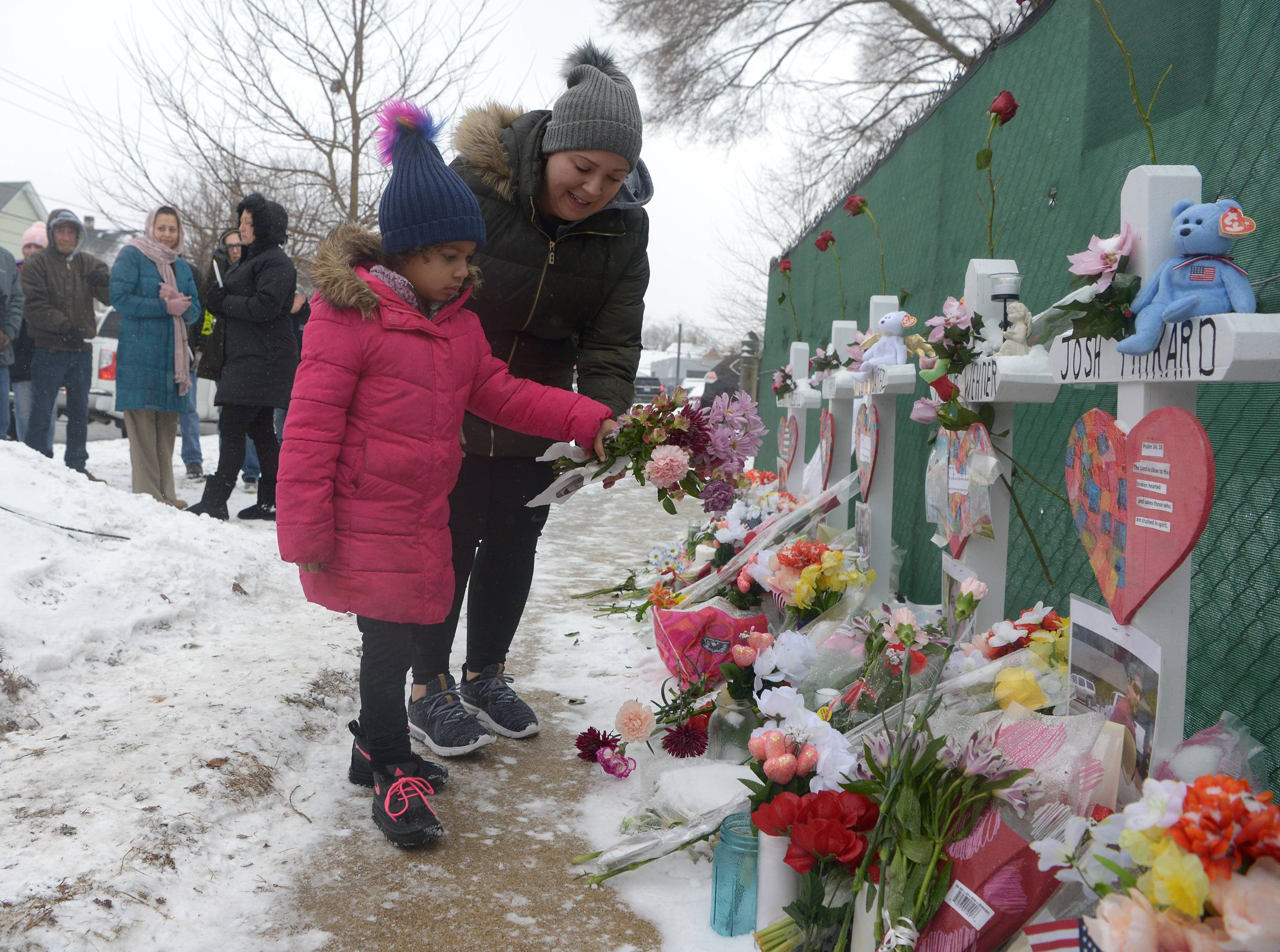 Mourners place a flower at the crosses outside the Henry Pratt Co. in Aurora on Sunday in memory of the five employees killed on Friday.