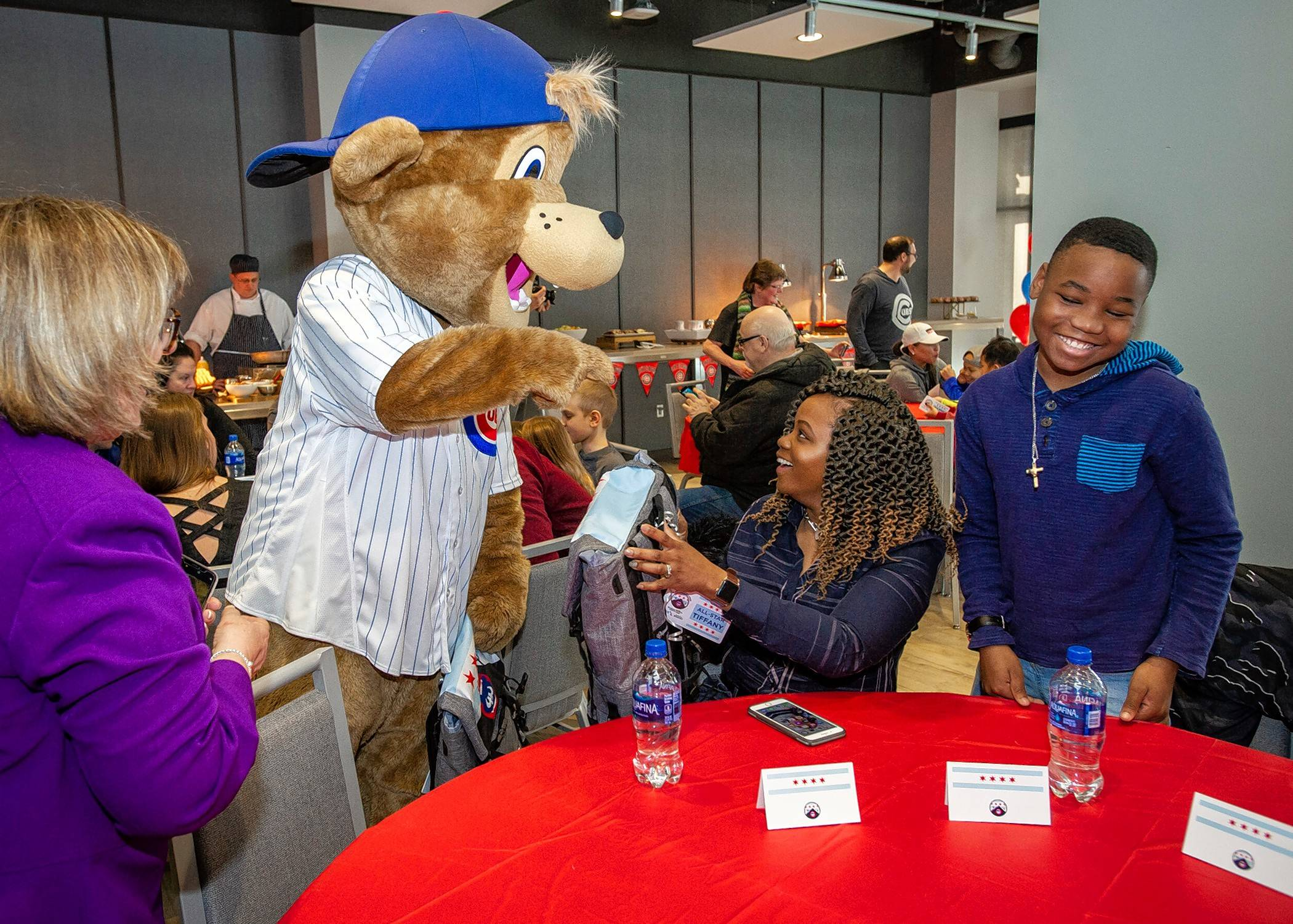 Jonathan Holiday of Bartlett, right, and his mother, Tiffany, meet Clark the Cub at the Cubs front office building Monday. Jonathan and six other children who are patients at Advocate Children's Hospital in Park Ridge were selected for a trip to Cubs spring training in Mesa, Arizona.