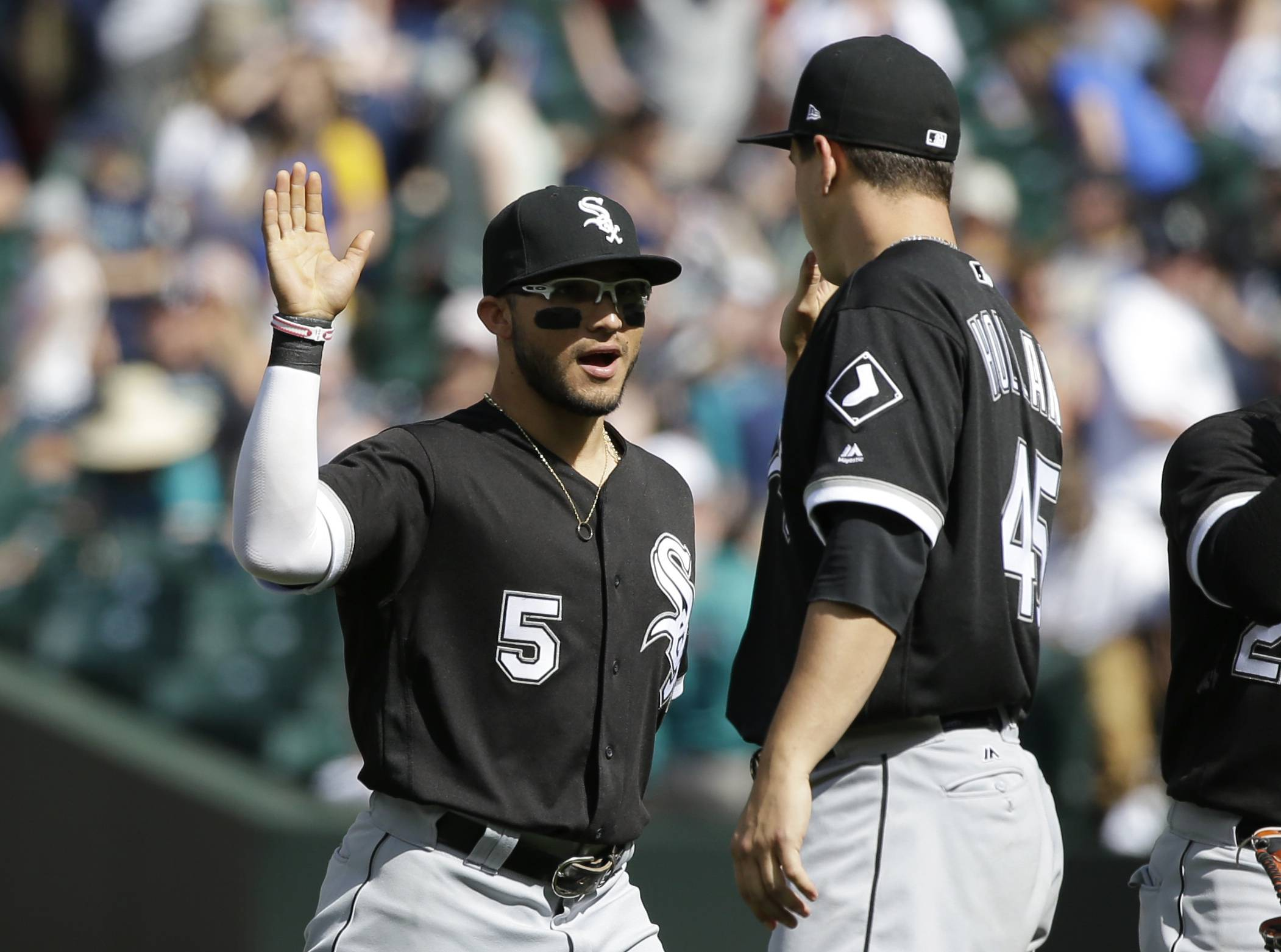 Chicago White Sox's Yolmer Sanchez (5) greets starting pitcher Derek Holland after the White Sox beat the Seattle Mariners 8-1 in a baseball game, Sunday, May 21, 2017, in Seattle.