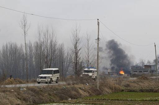 Vehicles belonging to Indian policemen are seen as flames and smoke billows from a residential building where militants are suspected to have taken refuge during a gun battle in Pulwama, south of Srinagar, Indian controlled Kashmir, Monday, Feb. 18, 2019. Tensions continued to rise in the aftermath of a suicide attack in disputed Kashmir, with seven people killed Monday in a gunbattle that broke out as Indian soldiers scoured the area for militants.