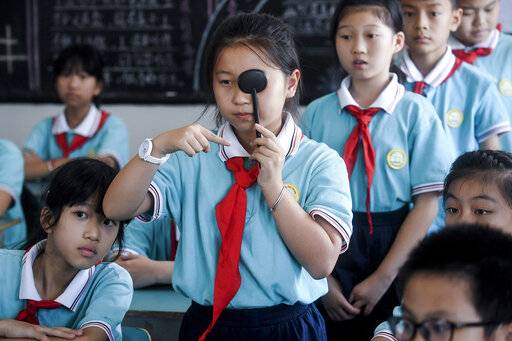 In this Sept. 4, 2018, photo released by Xinhua News Agency, students line-up to get eyesight test at a primary school in Donglin Township of Huzhou City, east China's Zhejiang Province. An eastern Chinese province plans to ban teachers from assigning homework to be completed on cellphone apps as part of efforts to preserve students' eyesight. Zhejiang province issued a draft regulation last week and is seeking public comment. (Xu Yu/Xinhua via AP)