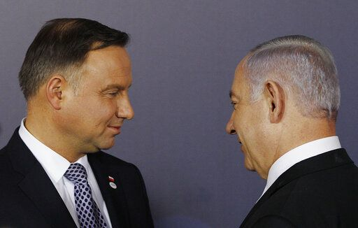 FILE - In this Wednesday, Feb. 13, 2019 file photo, Polish President Andrzej Duda , left, and Israeli Prime Minister Benjamin Netanyahu, talk after a group photo during a two-day international conference on the Middle East, at the Royal Castle in Warsaw, Poland. An off-hand comment by Netanyahu in Warsaw about Poland and the Holocaust looks to overshadow a summit of central European leaders this week in Israel. Poland's abrupt decision Sunday to downgrade its participation in the Visegrad conference suddenly cast a pall gathering.