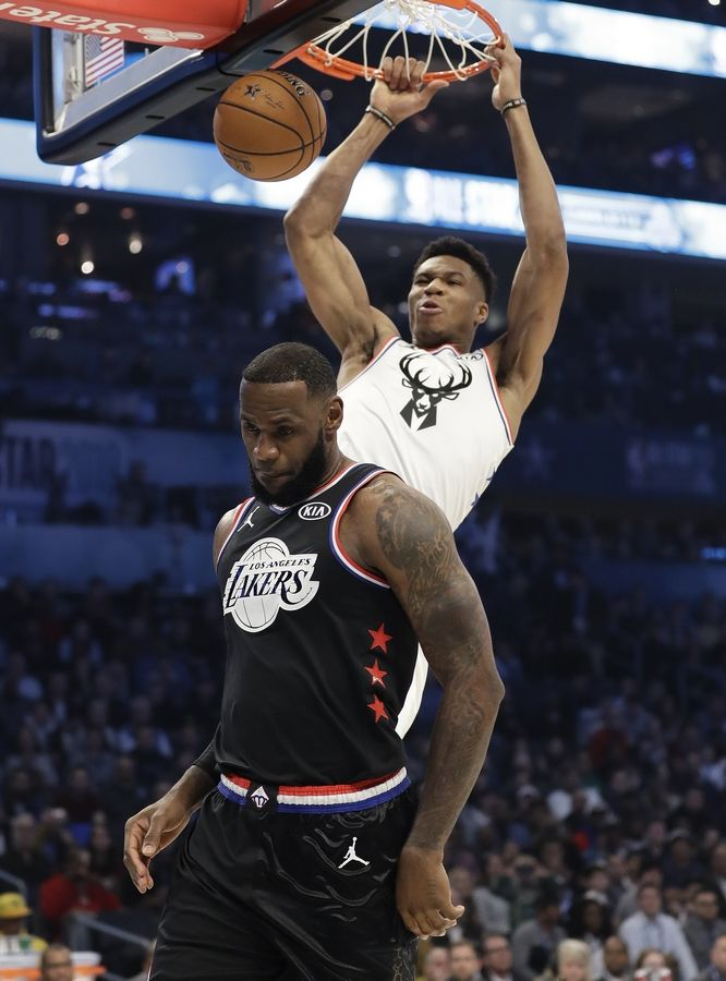 Team Giannis' Giannis Antetokounmpo, of the Milwaukee Bucks, dunks the ball against Team LeBron's LeBron James, of the Los Angeles Lakers, during the first half of an NBA All-Star basketball game, Sunday, Feb. 17, 2019, in Charlotte, N.C.