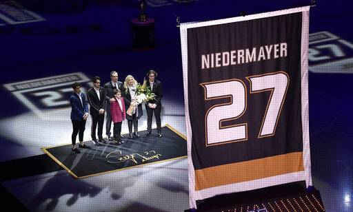 Former Anaheim Ducks defenseman Scott Niedermayer watches along with his family as his jersey is retired prior to an NHL hockey game between the Ducks and the Washington Capitals Sunday, Feb. 17, 2019, in Anaheim, Calif. (AP Photo/Mark J. Terrill)