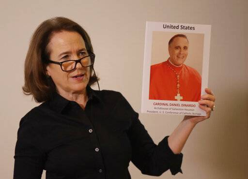 Anne Barrett Doyle, co-director of BishopAccountability.org group, holds up a photo of Cardinal Daniel DiNardo, the archbishop of Houston-Galveston and the president of the U.S. Conference of Catholic Bishops, during a press conference at the foreign press association in Rome, Tuesday Feb. 19, 2019. DiNardo has been accused by victims of downplaying their accusations against Rev. Manuel La Rosa-Lopez, who was charged in September with four counts of indecency with a child and has been criticized for allowing the Rev. John T. Keller, to celebrate Mass even though later in the day his name appeared on a list released by the church of credibly accused priests. (AP Photo/Alessandra Tarantino)