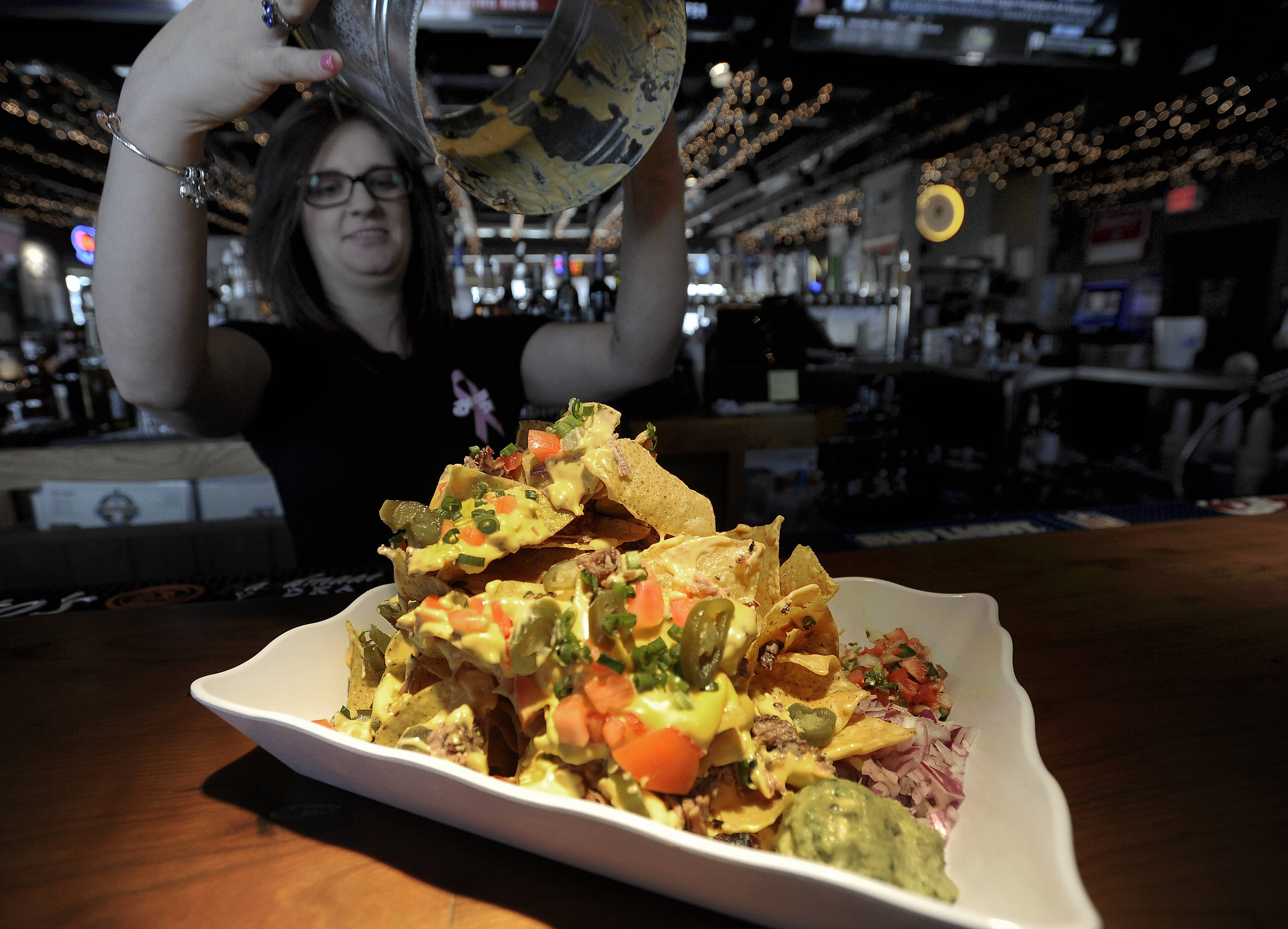 Beacon Tap bartender Breanna Weegens entertains the Tuesday afternoon lunch crowd as she lifts the trash can to reveal the Trash Can Nachos.