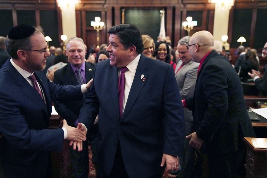 Gov. J.B. Pritzker is congratulated by lawmakers after delivering his first budget address to a joint session of the legislature Wednesday in Springfield.