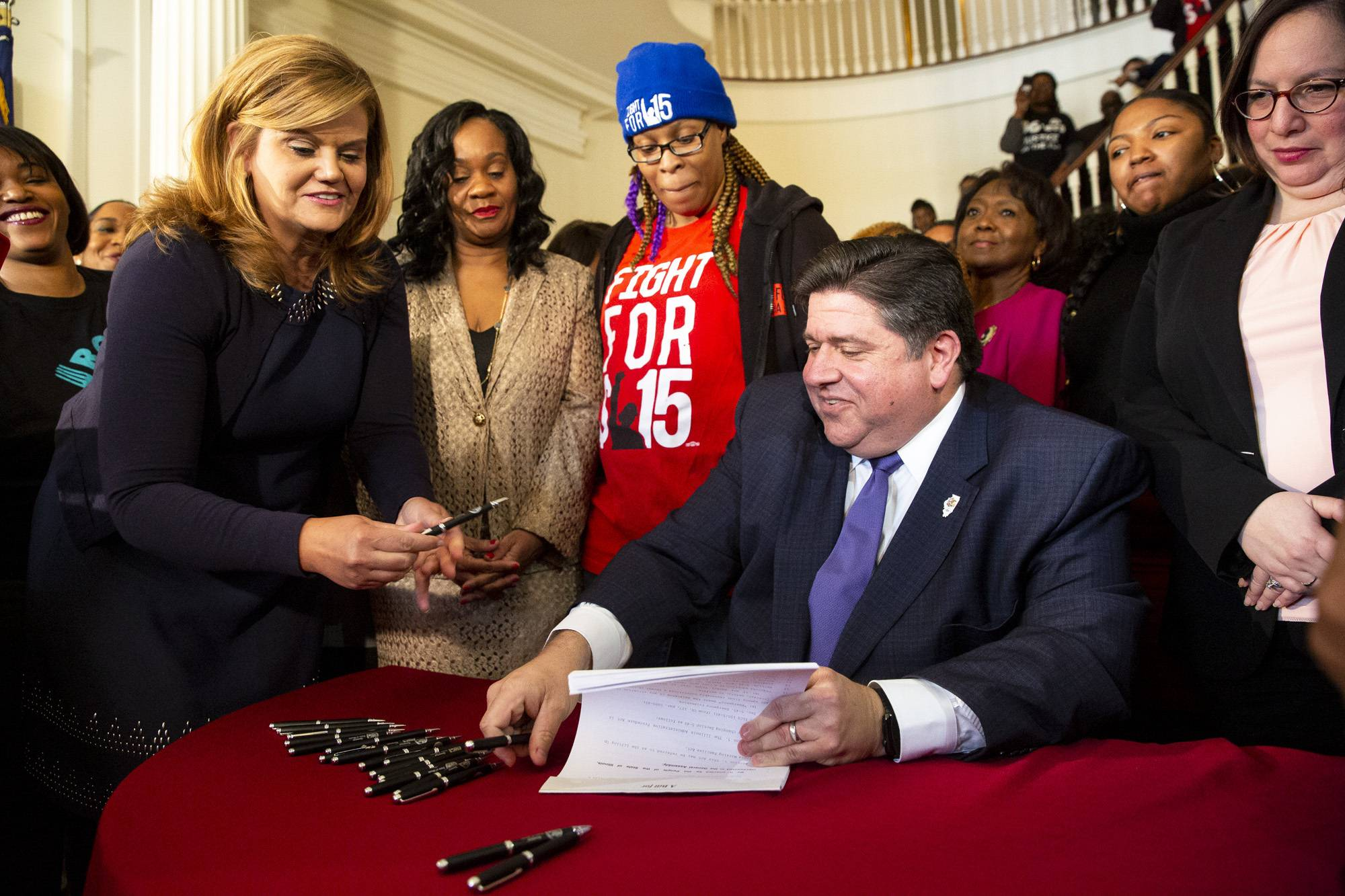 M.K. Pritzker hands pens to her husband, Gov. J.B. Pritzker, Tuesday as he signs SB1 raising the minimum wage in Illinois. Pritzker wants to legalize recreational marijuana and sports betting.