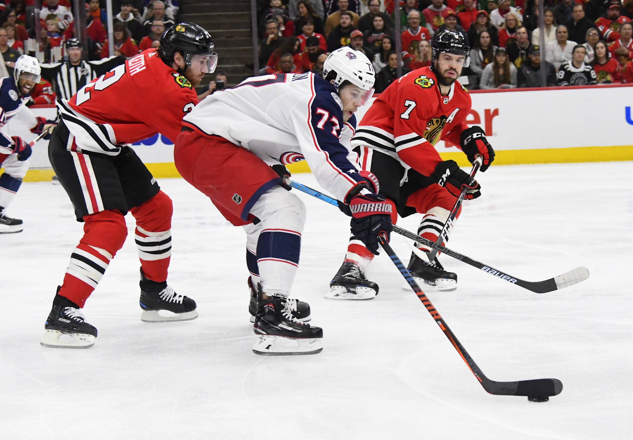 Columbus Blue Jackets right wing Josh Anderson (77) fights for the puck against Chicago Blackhawks defensemen Duncan Keith (2) and Brent Seabrook (7) during the first period of an NHL hockey game Saturday, Feb. 16, 2019, in Chicago. (AP Photo/Matt Marton)