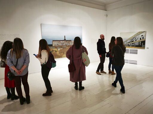 In this photo taken on Sunday, Feb. 17, 2019, visitors attend an exhibition by Russian artist Pavel Otdelnov in Moscow, Russia . Pavel Otdelnov, a Russian artist who grew up in Dzerzhinsk, the center of the nation's chemical industries 355 kilometers (220 miles) east of Moscow, focused on the city, one of the most polluted in Russia, in his new 'Promzona' art show.
