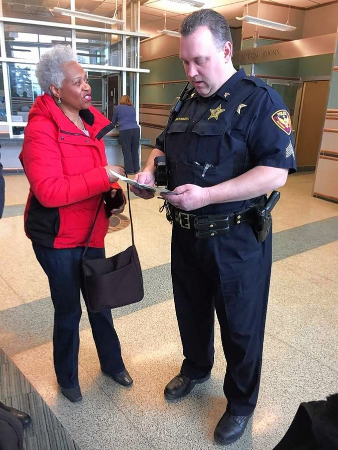 Regina Brent of Aurora, president and founder of Unity Partnership, explains her group's efforts Thursday to promote understanding and improved relationships between police departments and diverse communities to Aurora police Sgt. Andrew Wolcott.