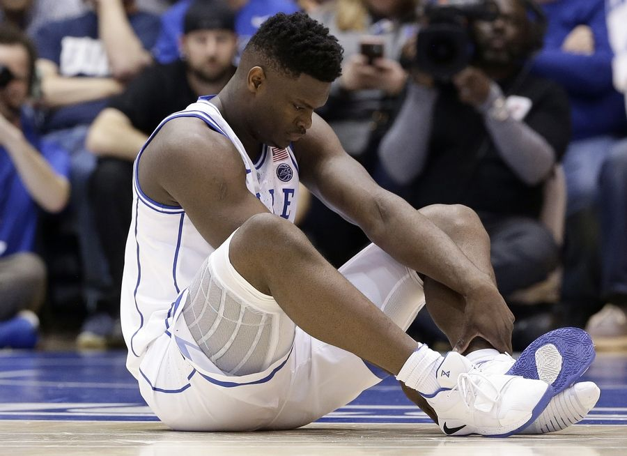 Duke's Zion Williamson sits on the floor Wednesday following an injury against North Carolina.