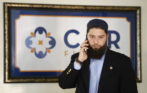 Hassan Shibly, attorney for Hoda Muthana, the Alabama woman who left home to join the Islamic State group in Syria, speaks on a phone before a news conference Wednesday, Feb. 20, 2019, in Tampa, Fla. United States Secretary of State Mike Pompeo said Muthana is not a U.S. citizen and will not be allowed to return to the United States.