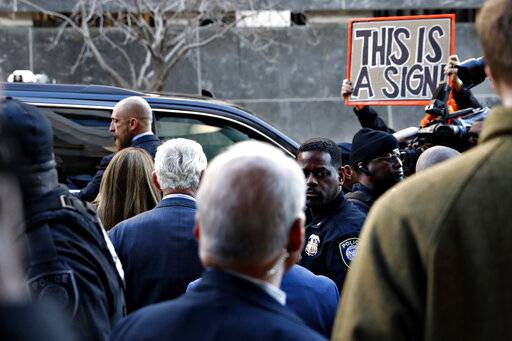 Former campaign adviser for President Donald Trump, Roger Stone, center left, walks to his vehicle as he leaves federal court Thursday, Feb. 21, 2019, in Washington, between members of the media, security, and protesters. A judge has imposed a full gag order on Trump confidant Roger Stone after he posted a photo on Instagram of the judge with what appeared to be crosshairs of a gun.