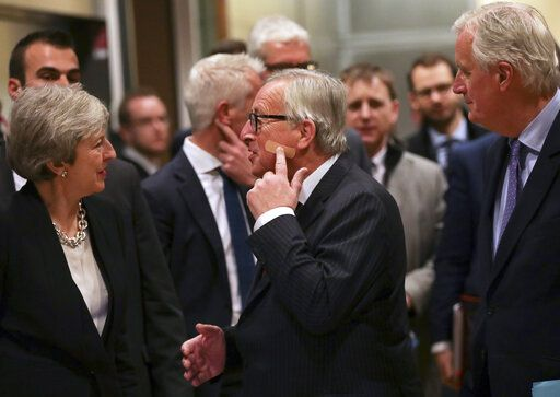 European Commission President Jean-Claude Juncker, center, points to a band aid on his cheek as he speaks with British Prime Minister Theresa May, left, prior to a meeting at EU headquarters in Brussels, Wednesday, Feb. 20, 2019. European Commission President Jean-Claude Juncker and British Prime Minister Theresa May meet Wednesday for their latest negotiating session to seek an elusive breakthrough in Brexit negotiations.