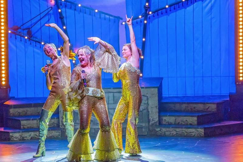 "Donna and the Dynamos, featuring Tanya (McKinley Carter), left, Donna (Susie McMonagle) and Rosie (Elizabeth Ledo), sing ""Waterloo"" in the encore finale of the ABBA jukebox musical ""Mamma Mia!"" at Drury Lane Theatre in Oakbrook Terrace."
