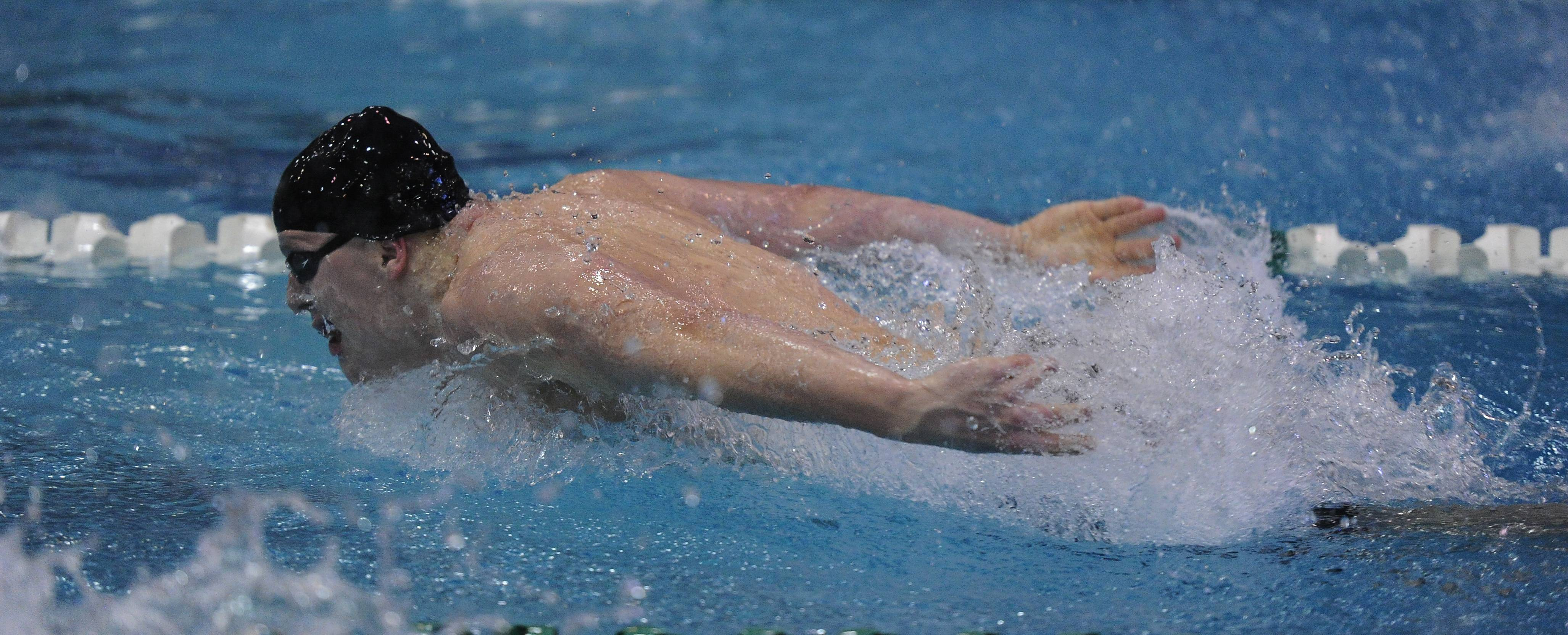 William Myhre of St. Charles North wins 1st place in heat 6 of the 100-yard butterfly in the IHSA state boys swimming preliminaries at New Trier High School on Friday.