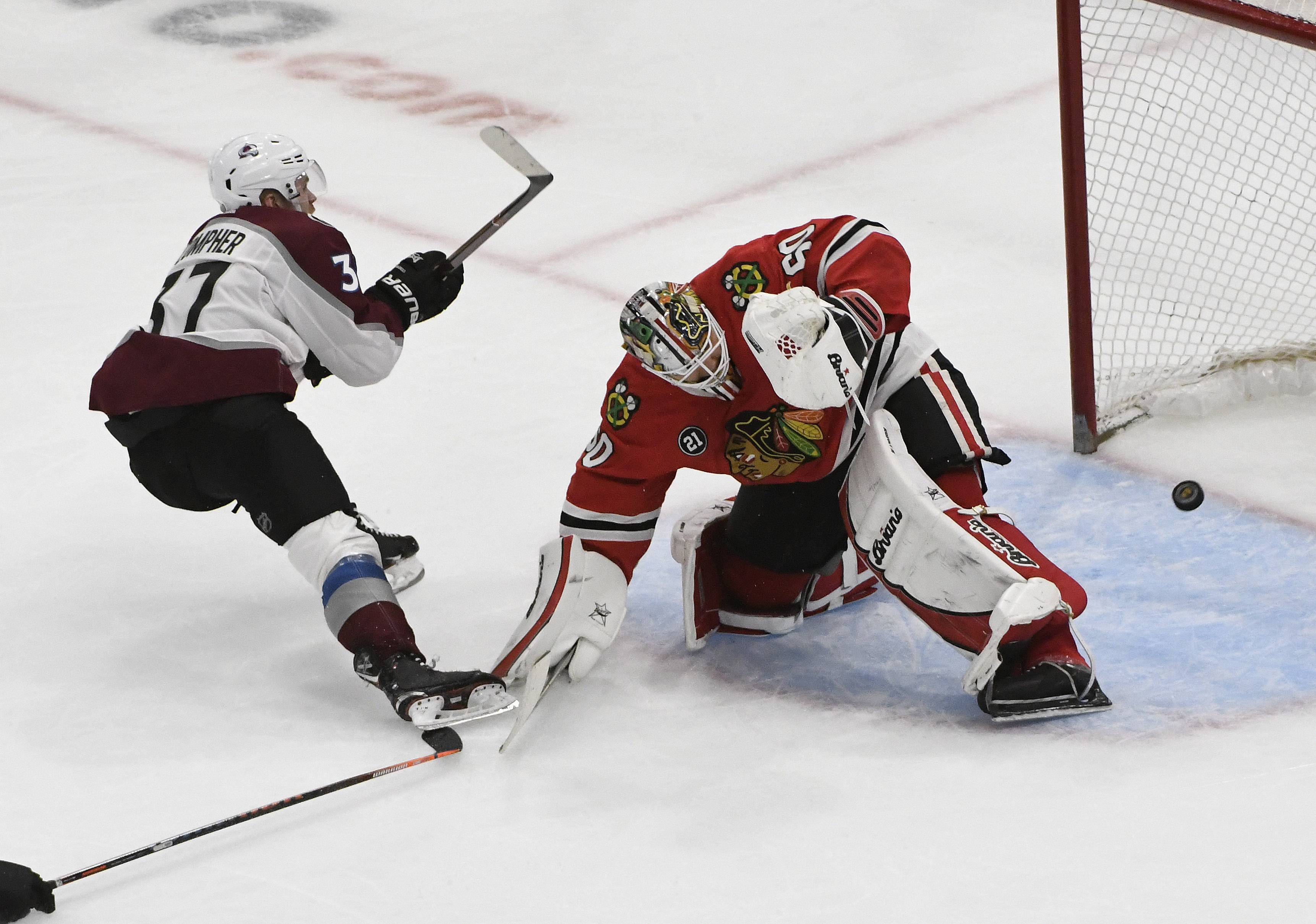 Colorado Avalanche left wing J.T. Compher (37) scores a goal on Chicago Blackhawks goaltender Collin Delia (60) during the third period of an NHL hockey game Friday, Feb. 22, 2019, in Chicago. (AP Photo/David Banks