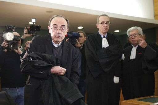 FILE - In this Jan.7, 2019 file photo, cardinal Philippe Barbarin, center, takes his seat as he arrives at the Lyon courthouse with his lawyers : Jean-Felix Luciani, 2nd right, and Andre Soulier, right, to attend his trial, in Lyon, central France. Still coming to terms with their responsibility in the clerical sex abuse scandals that have rocked the Catholic church, French bishops have finally accepted the principle of awarding a financial compensation to victims in France.