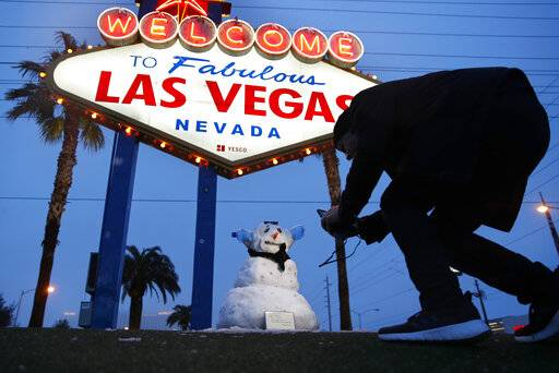 "A man, who declined to give his name, takes a picture of a small snowman at the ""Welcome to Fabulous Las Vegas"" sign along the Las Vegas Strip, Thursday, Feb. 21, 2019, in Las Vegas. Las Vegas is getting a rare taste of real winter weather, with significant snowfall across the metro area in the first event of its kind since record keeping started back in 1937. (AP Photo/John Locher)"