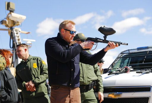 Acting Secretary of Defense Patrick Shanahan, center, fires a modified painted ball gun during a tour of the US-Mexico border at Santa Teresa Station in Sunland Park, N.M., Saturday, Feb. 23, 2019. Top defense officials toured sections of the U.S.-Mexico border Saturday to see how the military could reinforce efforts to block drug smuggling and other illegal activity, as the Pentagon weighs diverting billions of dollars for President Donald Trump's border wall.