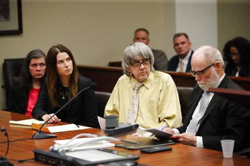 "David Turpin, second from right, and wife, Louise, far left, listen to their charges as they are joined by their attorneys, Allison Lowe, second from left, and David Macher in a courtroom Friday, Feb. 22, 2019, in Riverside, Calif. The California couple who shackled some of their 13 children to beds and starved them pleaded guilty Friday to torture and other abuse in a case dubbed a ""house of horrors."""