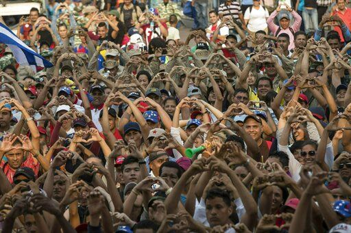 "Government supporters flash heart-hand signals during the ""Hands off Venezuela"" concert at the Tienditas International Bridge, in Venezuela on the border with Colombia, Friday, Feb. 22, 2019.  Venezuela's power struggle is set to convert into a battle of the bands Friday when musicians demanding Nicolas Maduro allow in humanitarian aid and those supporting the embattled leader's refusal sing in rival concerts being held at both sides of a border bridge where tons of donated food and medicine are being stored."