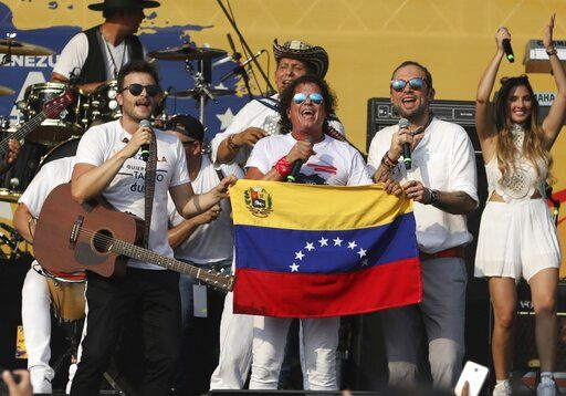 "Gusi, from left, Carlos Vives and Santiago Cruz, hold a Venezuelan national flag as they perform at the ""Live Aid Venezuela"" concert at the Tienditas International Bridge on the outskirts of Cucuta, Colombia, Friday, Feb. 22, 2019, on the border with Venezuela. British billionaire Richard Branson organized the mega concert, which features dozens of Latin musicians performing on a giant stage on one side of what Colombian authorities have renamed the ""Unity"" bridge."