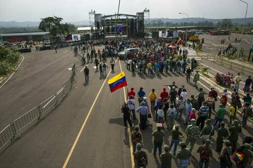"Government supporters gather during the first day of the ""Hands off Venezuela"" three-day music festival at the Tienditas International Bridge, in Urena, Venezuela, Friday, Feb. 22, 2019, on the border with Colombia. Venezuela's power struggle is set to convert into a battle of the bands Friday when musicians demanding Nicolas Maduro allow in humanitarian aid and those supporting the embattled leader's refusal sing in rival concerts being held at both sides of a border bridge where tons of donated food and medicine are being stored."