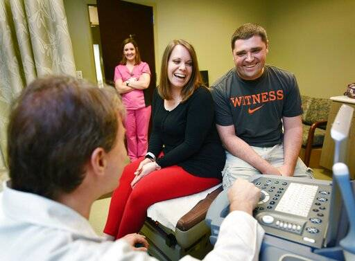 In this 2016 photo, Trisha and Brett Gibson laughs with Dr. Preston Parry, left, while reviewing Trisha's sonogram at a University of Mississippi Medical Center's Women's Specialty Clinic in Flowood, Miss. (Joe Ellis/The Clarion-Ledger via AP)