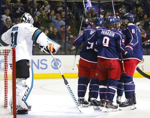 Columbus Blue Jackets players celebrate their goal against San Jose Sharks' Martin Jones during the second period of an NHL hockey game Saturday, Feb. 23, 2019, in Columbus, Ohio.