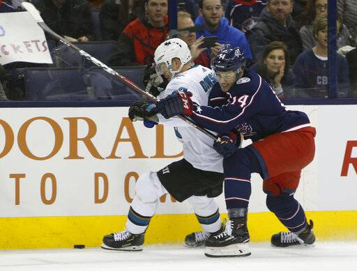 San Jose Sharks' Joonas Donskoi, left, of Finland, and Columbus Blue Jackets' Dean Kukan, of Switzerland, fight for the puck during the first period of an NHL hockey game Saturday, Feb. 23, 2019, in Columbus, Ohio.