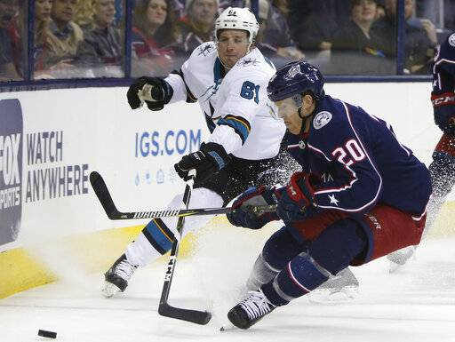 San Jose Sharks' Justin Braun, left, and Columbus Blue Jackets' Riley Nash chase the puck during the second period of an NHL hockey game Saturday, Feb. 23, 2019, in Columbus, Ohio.