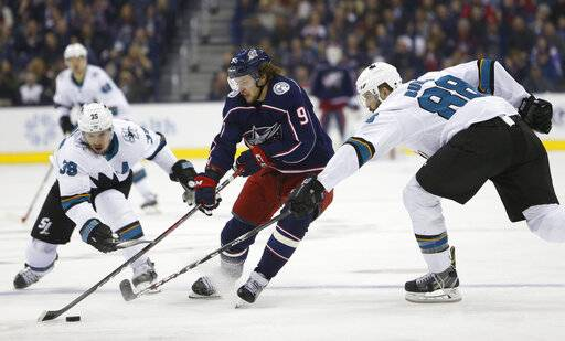 Columbus Blue Jackets' Artemi Panarin, center, of Russia, carries the puck across the blue line between San Jose Sharks' Logan Couture, left, and Brent Burns during the second period of an NHL hockey game Saturday, Feb. 23, 2019, in Columbus, Ohio.